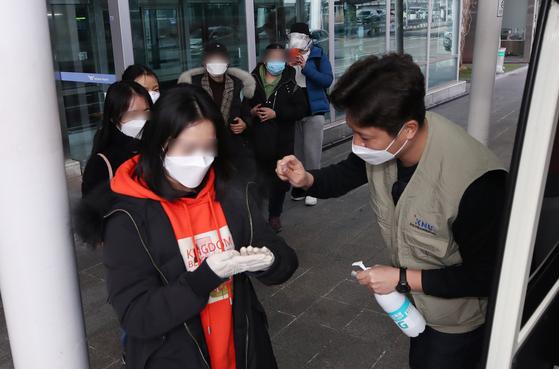 24일 인천국제공항 1터미널에서 입국한 강원대 중국인 유학생들이 학교에서 마련한 버스에 탑승하기 전 손과 몸을 소독하고 있다. [연합뉴스]