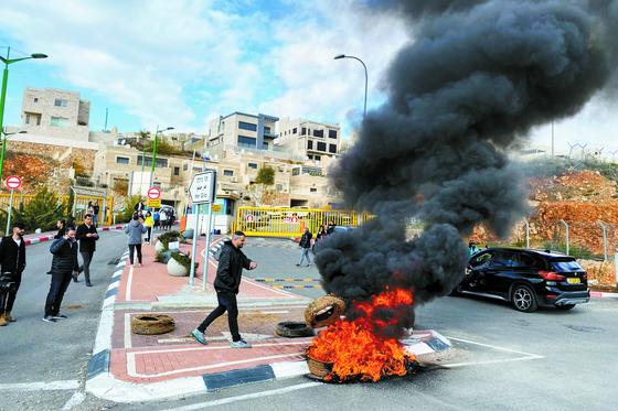 이스라엘 가자지구 서안의 유대인 정착촌에서 현지 주민들이 한국 순례객들의 코로나19 바이러스 감염 소식에 항의하면서 타이어를 불태우고 있다. [로이터=연합뉴스]