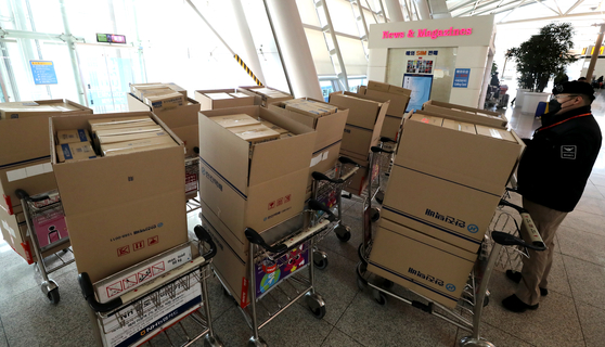 지난 6일 오전 인천국제공항 여객터미널 출국장 입구에 마스크 박스가 쌓여있는 가운데 인천공항 경비 관계자들이 마스크를 유실물센터로 옮기는 모습. 이 사진은 기사와 관련이 없습니다.[뉴스1]