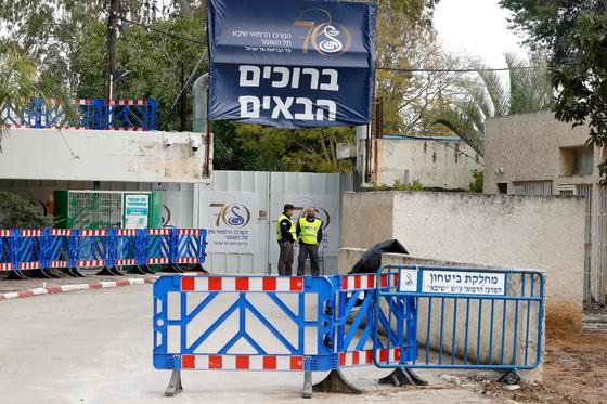 지난 21일 이스라엘의 도시 라마트간의 한 병원 문 앞에서 사람들이 경비를 서고 있다. 이 병원에는 이스라엘의 첫 신종 코로나 감염자가 격리돼 있다. 해당 감염자는 일본 크루즈 다이아몬드 프린세스호에 갇혀 있다가 이스라엘로 송환된 이다. 이스라엘 정부는 일본에서 온 송환자 모두를 14일간 현지 병원에 격리시켰다. [AFP=연합뉴스]