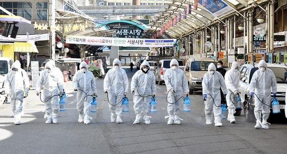 신종 코로나바이러스 감염증(코로나19)이 확산되고 있는 23일 오후 대구 중구 서문시장에서 코로나19 여파로 임시휴업을 한 상가연합회 관계자들이 방역작업을 하고 있다. [뉴시스]