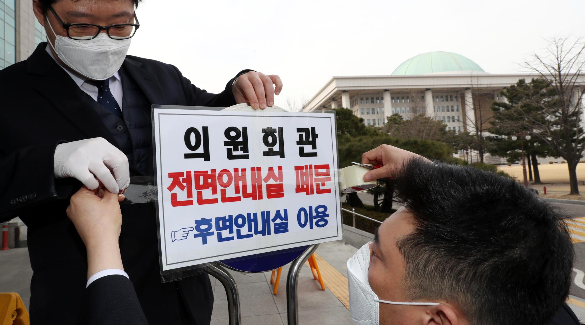 24일 국회 직원들이 의원회관 안내실 폐문을 알리는 문구를 붙이고있다. 임현동 기자