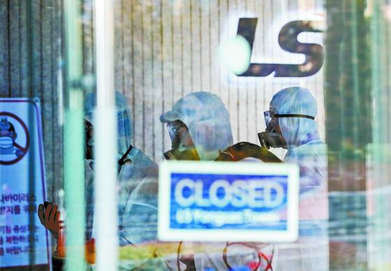 25일 신종 코로나바이러스 감염증(코로나19) 확진자가 발생한 서울 용산구 LS용산타워에서 방역업체 관계자들이 방역작업을 하기 위해 건물 안으로 들어가고 있다. [뉴스1]