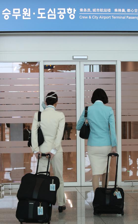 객실 승무원 1명이 신종 코로나바이러스 감염증(코로나19) 확진 판정을 받은 대한항공이 26일 임산부 직원들에게 재택근무를 하도록 했다.  대한항공은 이날부터 임산부 직원에게 재택근무를 하도록 하고, 현장 접객 직원을 제외한 일반 직원의 경우 27일부터 자율적으로 재택근무를 하도록 사내에 공지했다.   사진은 이날 영종도 인천국제공항 2터미널에서 이동하는 대한항공 승무원들. [연합뉴스]