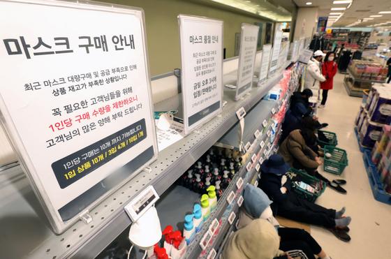 신종 코로나바이러스 감염증 (코로나19) 확진자가 1000명을 넘어선 26일 서울 한 마트에 마스크를 구매하려는 시민들이 판매를 기다리며 줄지어 앉아 있다. [뉴스1]