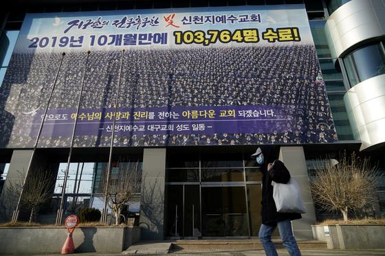 로이터통신이 22일 보도한 한국의 대구 신천지 교회의 모습. 마스크를 쓴 시민이 신천지예수교회 앞을 지나고 있다. [로이터=연합뉴스]