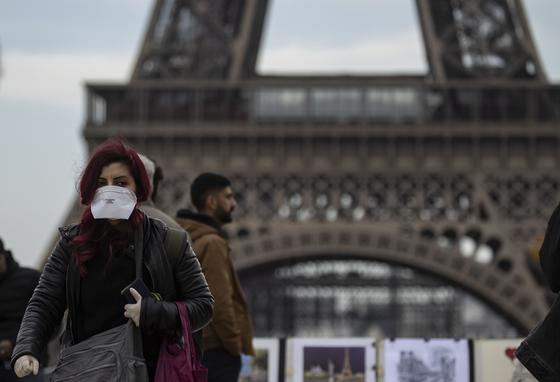 지난 15일 프랑스 파리 에펠탑 앞에서 마스크를 쓴 시민이 걸어가고 있다. EPA=연합뉴스