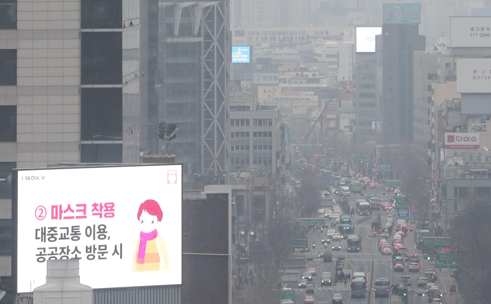 지난 21일 오후 서울 종로에서 코로나19 관련 전광판 뒤로 시내가 뿌옇게 보이고 있다. 연합뉴스