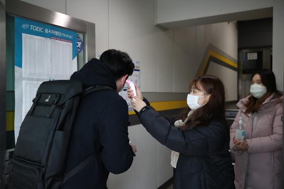지난 9일 오전 토익시험이 열린 서울시내 한 시험장에서 코로나19 확산 방지 등을 위해 관계자들이 수험생들의 체온을 측정하고 있다. [연합뉴스]