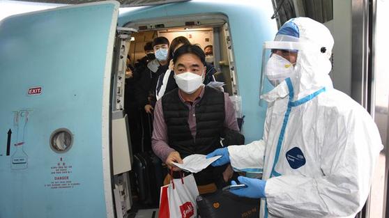 중국의 검역 요원이 25일 중국 칭다오 공항에 내린 승객들에 대해 체온 검사를 하고 있다. 칭다오는 24일부터 한국에서 오는 승객에 대한 검역 강화 조치를 시행하고 있다. [중국 신화망 캡처]