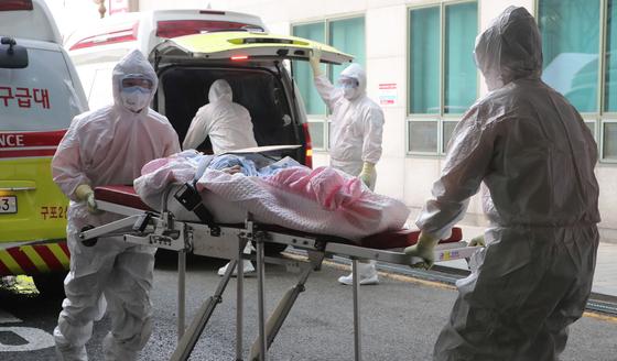 26일 부산소방본부 소속 119구급대원들이 부산 연산동 아시아드요양병원 환자를 부산의료원으로 이송하고 있다. 송봉근 기자