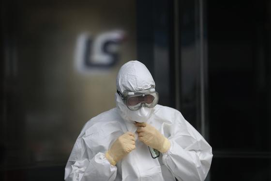 25일 용산구 방역 관계자가 LS타워 방역 작업을 마친 뒤 보호복을 벗고 있다. 연합뉴스