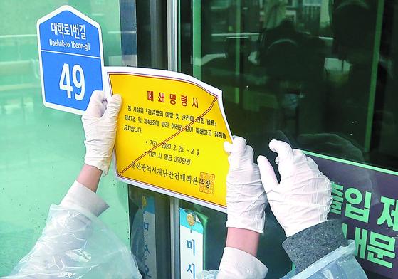 25일 오후 울산시 남구 무거동 신천지교회 출입문에 시 관계자들이 폐쇄명령서를 붙이고 있다. 연합뉴스