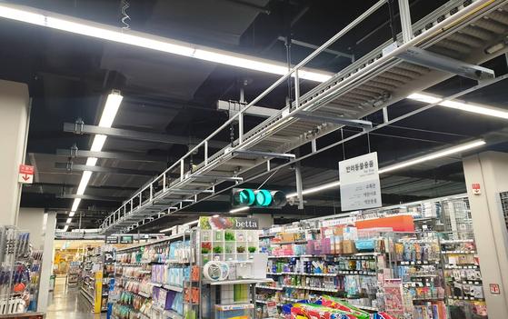 롯데마트 광교점 매장에 설치된 천장 컨베이어. 중계점은 135m, 광교점은 101m의 천장 컨베이어를 통해 피킹 상품을 패킹 장소로 보낸다. [사진 롯데쇼핑]