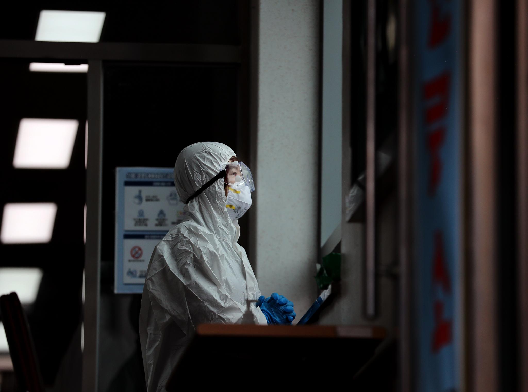 26일 오전 부산 동래구보건소 선별진료소에서 보건소 관계자가 코로나19 의심 환자가 잠시 없는 사이 창밖을 바라보며 두 손을 모으고 있다. [연합뉴스]