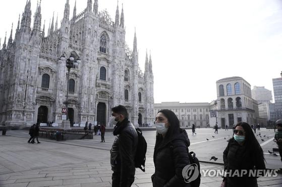 지난 23일(현지시간) 이탈리아 북부 밀라노에서 신종 코로나바이러스 감염증(코로나19) 우려로 마스크를 착용한 사람들이 고딕 대성당인 '두오모' 앞을 지나가고 있다. AP=연합뉴스