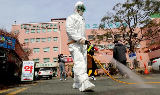 국내 코로나19 감염 확진자가 21일 하루 만에 100명이 추가돼 이날 오후 4시 기준 204명으로 늘어났다. 대구·경북 지역에서만 83명으로 집계됐다. 신천지대구교회 다음으로 많은 확진자가 나온 경북 청도대남병원에서 이날 오전 방호복을 입은 관계자가 방역 소독을 하고 있다. 방역 당국은 사망자 2명과 의료진 집단 감염까지 발생한 이 병원 시설을 폐쇄 조치했다. [연합뉴스]〈저작권자 ⓒ 1980-2020 ㈜연합뉴스. 무단 전재 재배포 금지.〉