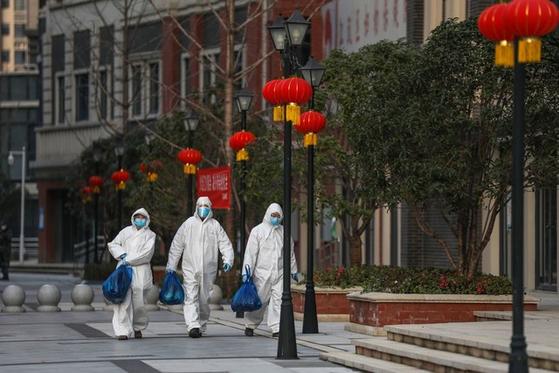 중국 후베이성 성도 우한에서 20일 방역요원들이 출입이 통제된 주민들에게 전달할 식재료를 들고 거리를 걷고 있다. [AFP=연합뉴스]