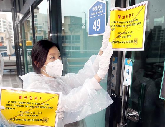 25일 오후 울산시 남구 무거동 신천지교회 출입문에 시 관계자가 폐쇄명령서를 붙이고 있다. 연합뉴스.