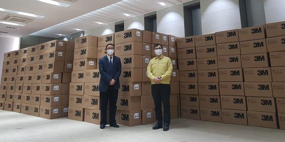 최영삼 주상하이 총영사(오른쪽)가 27일 상하이시 외사판공실 관계자와 함께 기증받은 마스크 앞에 서 기념사진 촬영을 하고 있다. 사진 주상하이 총영사관