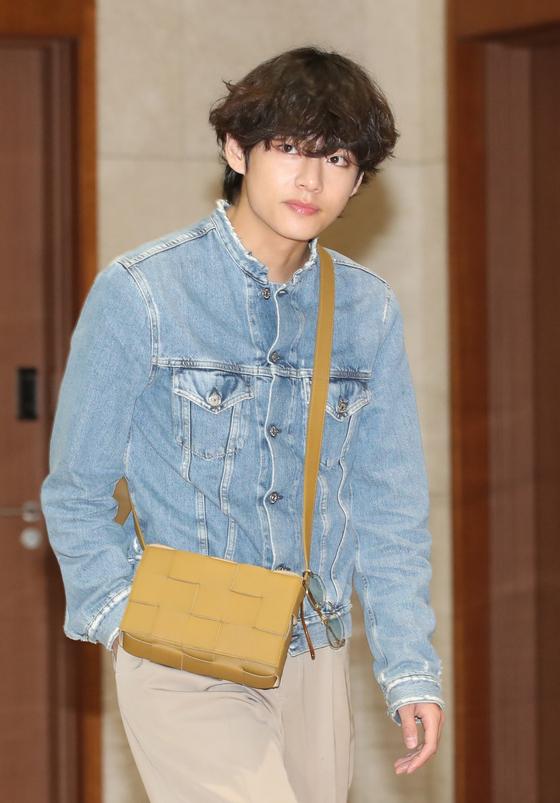 요즘 남자 아이돌의 '공항 패션'에는 어깨에 메는 작은 핸드백이 자주 등장한다. 여성용 핸드백 을 청재킷과 함께 착용한 방탄소년단 멤버 뷔. [뉴스1]