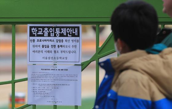 24일 서울 송파구의 한 초등학교 교문에 신종 코로나바이러스 감염증(코로나19) 확산 방지를 위해 학교시설 출입을 통제하는 내용의 안내문이 붙어 있다. [뉴스1]