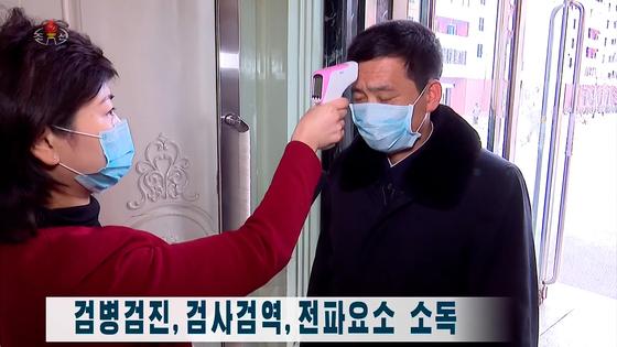 북한 조선중앙TV는 신종 코로나바이러스 감염증(코로나19) 예방 조치로 주민들에 대한 검병검진을 철저하게 하고 있다고 지난 27일 보도했다. 사진은 중앙TV 방송화면으로, 마스크를 낀 주민이 체온측정을 받고 있다. [연합뉴스]