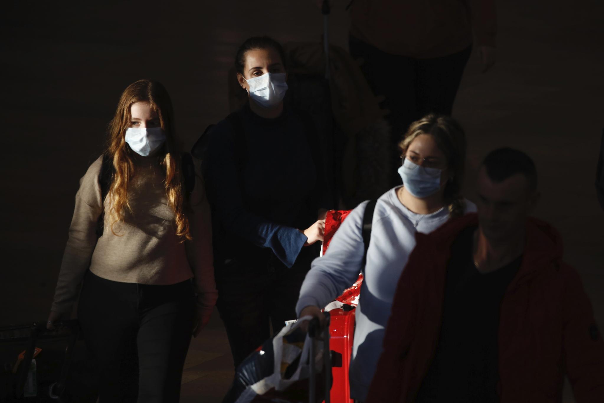 마스크를 쓴 여행객들이 27일(현지시간)) 이스라엘 텔아비브 인근 벤구리온 공항에 도착하고 있다. [AP=연합뉴스]