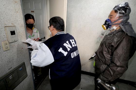 인하대 관계자들이 26일 오전 인천시 미추홀구 인하대학교 인근에서 자율격리중인 중국인 유학생의 숙소를 방문해 개인위생용품을 전달하고 있다.[뉴스1]