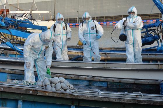 27일 오후 경북 북구 동빈부두에서 포항해양경찰서 관계자들과 한국해양구조협회 경북특수구조대원들이 정박 돼 있는 어선을 대상으로 신종 코로나바이러스 감염증(코로나19) 차단 방역을 실시하고 있다. 뉴스1