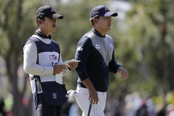 이경훈(오른쪽)이 28일 열린 PGA 투어 혼다 클래식 첫날 캐디와 함께 8번 홀에서 전략을 짜고 있다. [AP=연합뉴스]