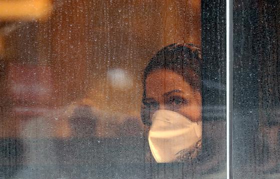이란의 수도 테헤란의 한 카페에서 지난 19일 마스크를 쓴 여성이 창 밖을 바라보고 있다. EPA=연합뉴스