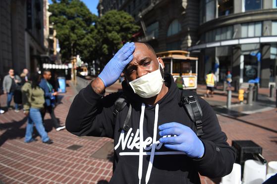 미국 샌프란시스코에서 27일(현지시간) 한 남성이 마스크와 보호 장갑을 끼고 있다. 이날 캘리포니아 북부에서 감염 경로가 밝혀지지 않은 신종 코로나 확진자가 나오면서 미국 정부가 한국 등으로부터 입국하는 사람 가운데 호흡기 증상을 보이는 사람에 대해 코로나 검사를 하기로 했다. [AFP=연합뉴스]