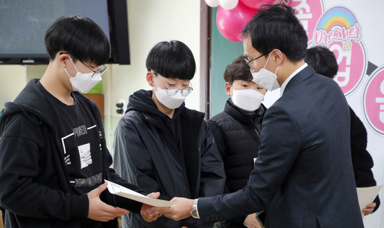 지난 7일 전북 전주시 전주동신초등학교에서 신종 코로나바이러스 감염증(코로나19) 확산 우려에 대한 예방조치로 졸업식이 학무모의 참석 없이 각 교실에서 실시된 가운데 마스크를 착용한 졸업생들이 상장을 받고 있다. [뉴스1]