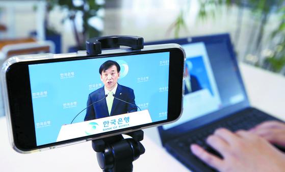 한국은행은 신종 코로나바이러스 감염증 확산으로 27일 열린 이주열 총재의 통화정책 방향 기자 간담회를 유튜브를 통해 진행했다. 한 기자가 휴대전화로 이 총재의 모습을 보고 있다. [연합뉴스]