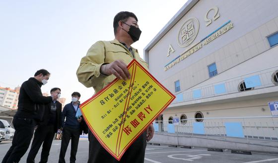 광주시와 북구청 관계자들이 27일 오후 광주 북구 오치동 신천지 베드로지성전(광주교회) 출입문에 시설 폐쇄를 알리는 행정처분서를 붙이고 있다. 뉴스1