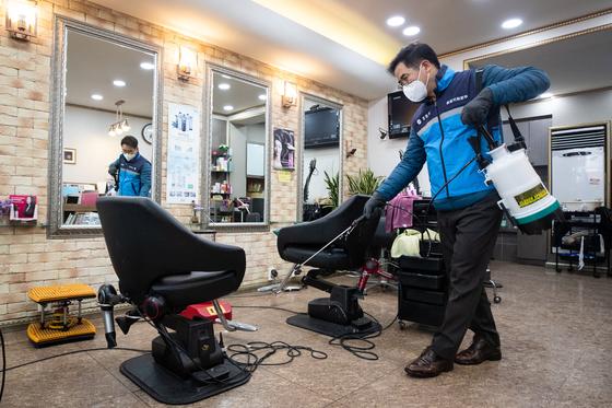 26일 서울 강동구 한 미용실에서 관계자가 방역작업을 하고 있다. [뉴스1]