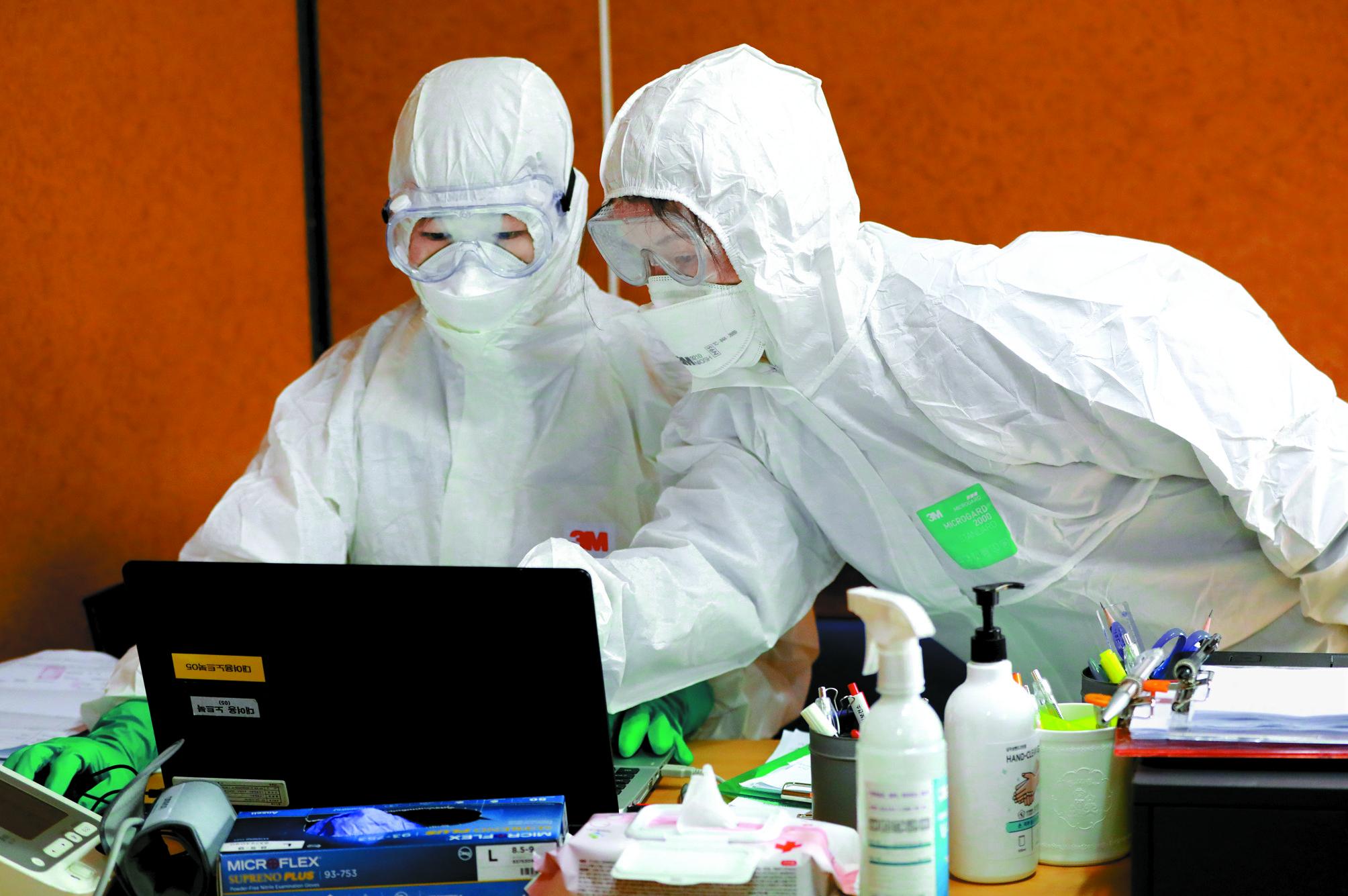 방역당국 관계자들이 28일 경기 김포시 사우동 김포보건소에 설치된 코로나 19 선별진료소에서 검체 채취를 하고 있다.뉴스1