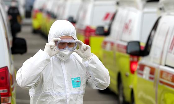 1일 오전 대구 달서구 두류정수장에서 환자 이송 지원을 나온 한 소방대원이 보호장비를 고쳐 쓰고 있다. 연합뉴스