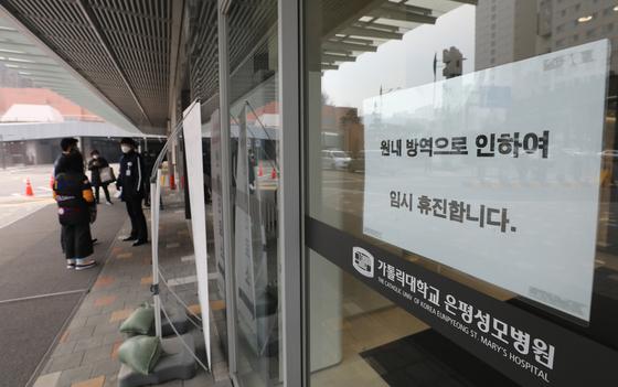 지난달 21일 서울 은평성모병원에서 환자 이동을 돕는 이송요원이 신종 코로나바이러스 감염증(코로나19) 진단검사에서 양성 판정을 받자 병원이 임시 폐쇄됐다. 뉴스1