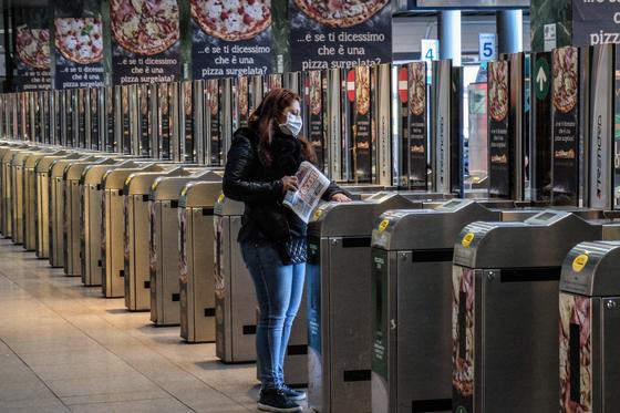 신종 코로나바이러스 감염증(코로나19) 확산으로 한산해진 이탈리아 밀라노의 기차역에서 24일(현지시간) 마스크를 쓴 한 여성이 개찰구로 들어가고 있다. [EPA=연합뉴스]