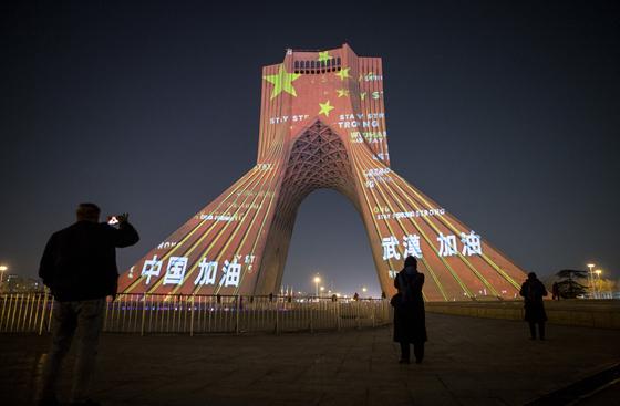 지난 2월 18일 이란 수도 테헤란에 있는 어저디(자유) 탑에 코로나19에 시달리는 중국과 우한을 격려하는 글귀를 비춘 장면. 이란과 중국의 돈독한 관계를 보여주는 장면이기도 하다. 이 행사 직후 이란에 코로나19가 확산하기 시작했다. 이 탑은 1978~79년 이란의 이슬람 혁명 당시 시민들이 모여 반정부 시위를 벌이던 곳이다. 신화=연합뉴스