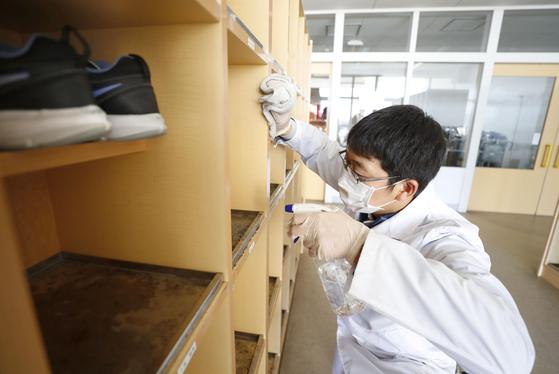 지난달 27일 일본 홋카이도 기타히로시마시의 한 공립 초등학교에서 관계자가 신발장을 소독하고 있다.   홋카이도에서는 이날부터 도내 대부분의 초등학교와 중학교가 휴교를 시작했다. [연합뉴스]