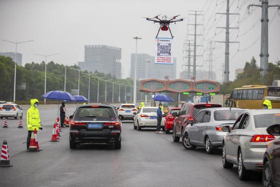 지난달 11일 광둥성 선전시로 이어진 고속도로 톨게이트에 스마트폰 프로그램을 내려받는 QR 코드를 매단 드론이 떠있다. 선전시는 8일 코로나19 방역을 위해 모든 운전자의 행적과 체온을 등록하는 온라인 시스템을 가동했다. [신화=연합뉴스]