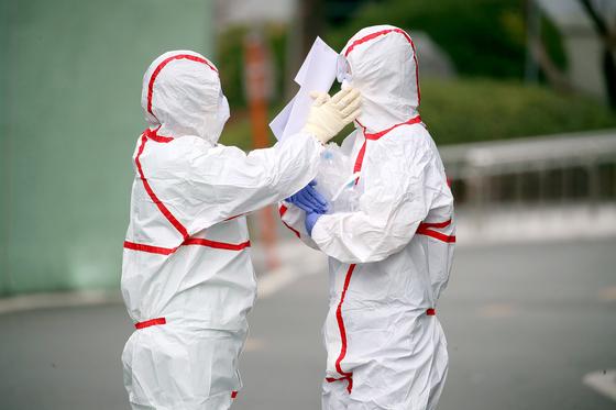 지난달 27일 오전 신종 코로나바이러스 감염증(코로나19) 지역거점병원인 계명대학교 대구동산병원에서 의료진이 근무 교대를 하기에 앞서 서로의 보호복을 점검하며 격려하고 있다. 뉴스1