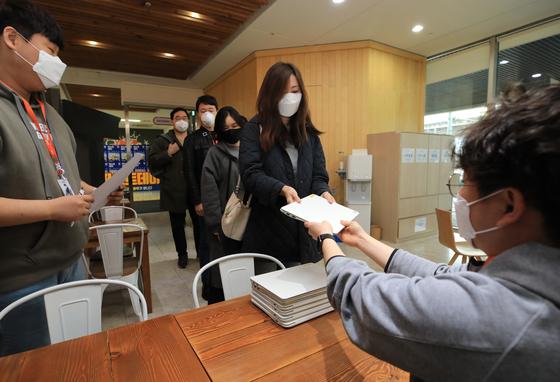 지단달 25일 티몬 직원들이 서울 강남구 본사에서 신종 코로나바이러스 감염증(코로나19) 위기경보 격상에 따른 재택근무를 위해 노트북을 수령하고 있다. 티몬은 직원들의 건강관리와 지역사회 전파 방지 차원에서 26일부터 28일까지 3일간 전 직원 재택근무를 실시했다. [뉴스1]