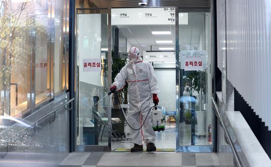 지난달 24일 오후 부산 연제구 아시아드요양병원과 같은 건물을 쓰는 1층 한 병원에서 병원 관계자가 방역하고 있다. 연합뉴스