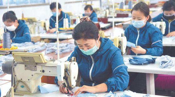 평양시 피복공업관리국 산하 여성직원들이 재봉틀을 이용해 천 재질의 마스크를 만들어 내고 있다. 북한은 코로나19 대응책으로 평소 옷을 만들던 주요 도시의 피복공장들을 마스크 생산 체제로 전환했다. [연합뉴스]