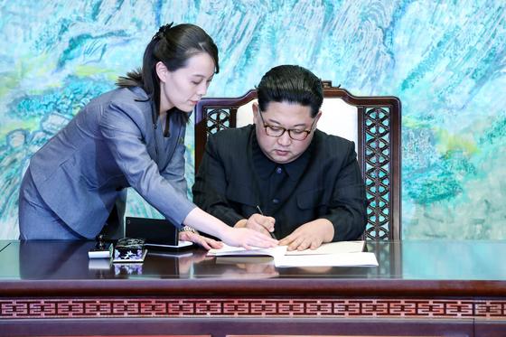 김정은 북한 국무위원장이 2018년 4월 27일 판문점 평화의 집에서 열린 '한반도의 평화와 번영, 통일을 위한 판문점 선언' 서명식에서 김여정 노동당 제1부부장의 도움을 받아 선언문에 서명을 하고 있다. [중앙포토]