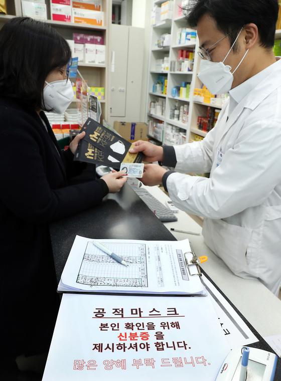 시민이 서울의 한 약국에서 신분증을 내고 공적 판매 마스크를 사고 있다. 뉴시스